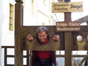 """Carl Gibson """"am Pranger"""" in Rothenburg ob der Tauber  - Ironische Reminiszenz an das Mittelalter"""